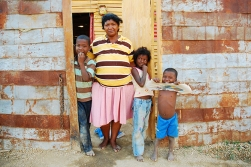 Una familia es retratada frente a su pequeño hogar