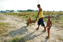Un padre lleva a su hijo en una carretilla.