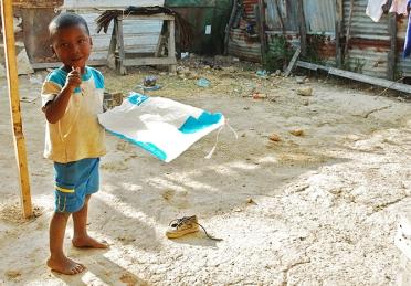 Un niño descalzo hace un papagayo.