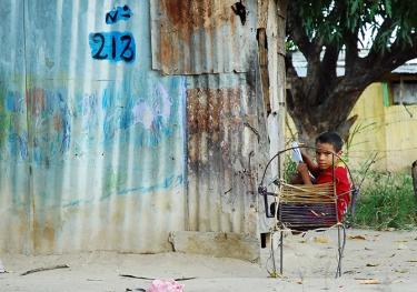 Un niño estudia sentado afuera de su hogar.