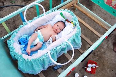 Un bebe montado sobre una cuna de madera